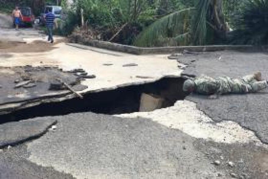 1st Lt. Erin Graham of the North Carolina National Guard inspects a washed out bridge in the small Puerto Rico community of Vallaja.