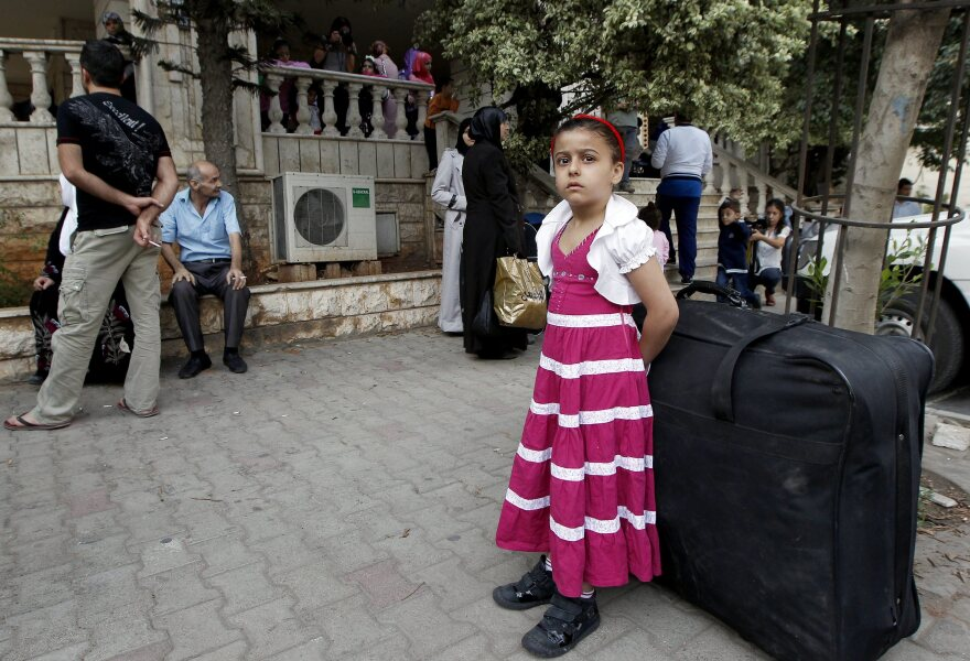 Syrian refugees wait in Beirut before a flight to Germany on Wednesday. More than 100 Syrians were on the flight, the first mass relocation program for Syrian refugees. Germany has agreed to take in 5,000 of them.