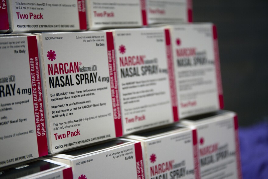 White and red boxes of Narcan stacked on a table.