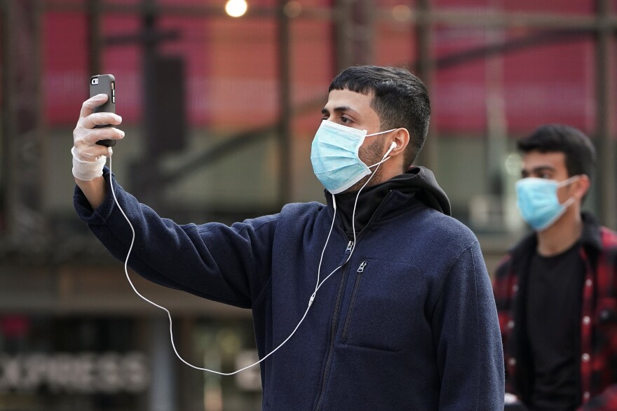 A man takes pictures as he wears a protective face mask at Times Square following the outbreak of COVID-19, in the Manhattan borough of New York City.