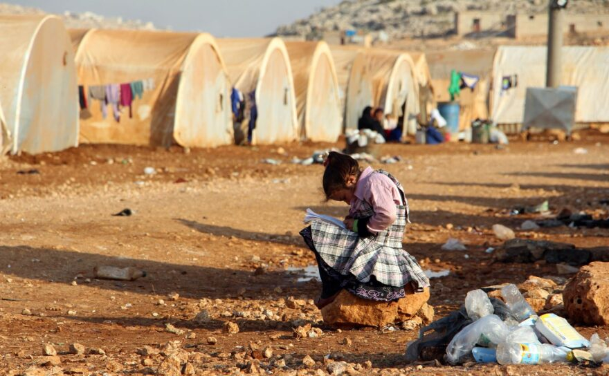 A girl writes in a notebook as she sits outside a tent at the Furat (Euphrates) camp for the displaced from Deir Ezzor, north of the town of Kafr Dariyan in the countryside of the northern province of Idlib.