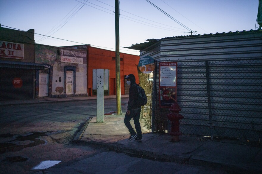 Cesar waits for a bus on an empty street corner in Ciudad Juárez.