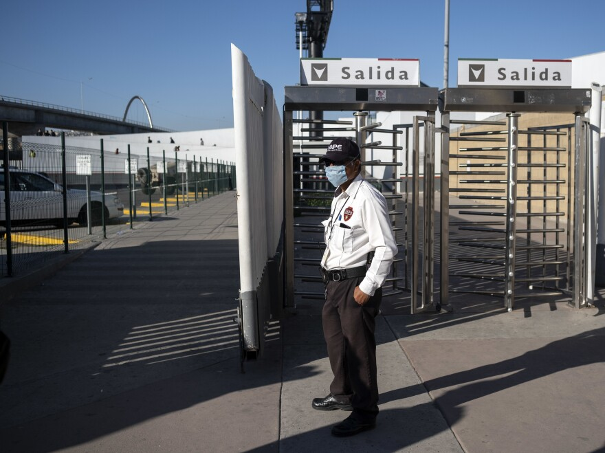 A security guard stands at the El Chaparral port of entry on the border in Tijuana, Mexico, last month. The U.S. and Mexico are said to be working out a deal to close their border to nonessential crossings.
