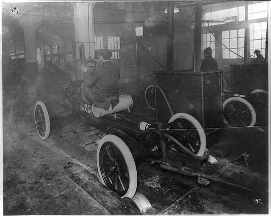 Photograph shows three men riding the skeleton of an automobile coming off the line with the rear wheels running on a revolving steel drum.