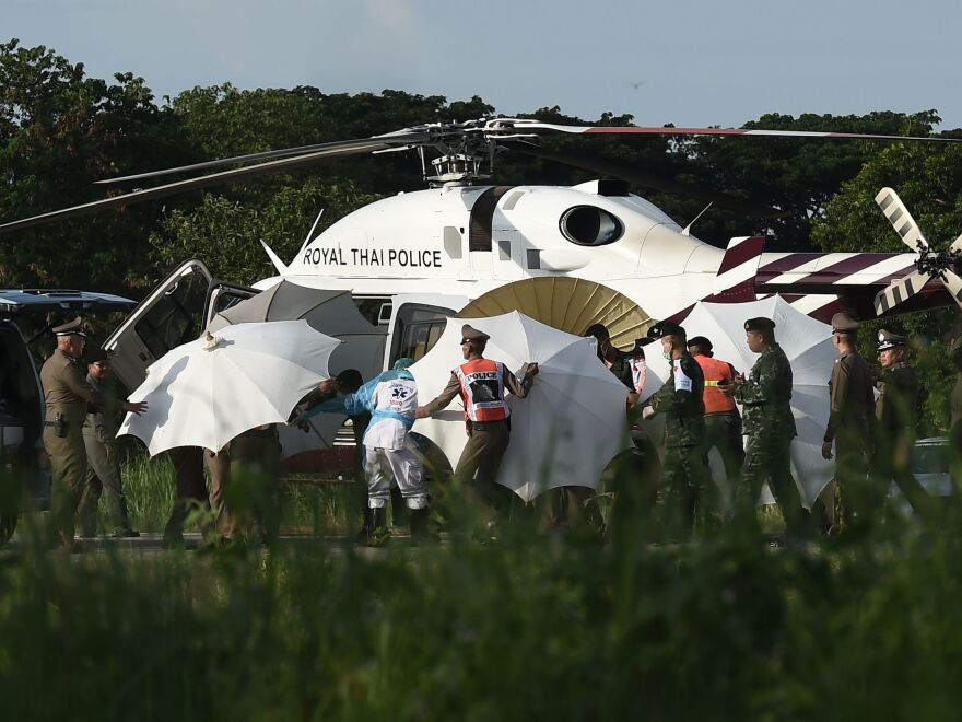 Police and military personnel use umbrellas to cover a stretcher as it is carried to a helicopter from an ambulance at a military airport in Chiang Rai, Thailand, on Monday, as rescue operations continued for those still trapped inside the cave in Khun Nam Nang Non Forest Park in the Mae Sai district.
