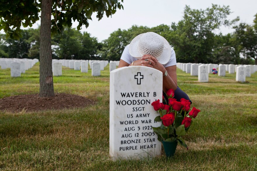 Joann Woodson kneels at the gravesite of her husband, Cpl. Waverly Woodson Jr., at Arlington National Cemetery in Arlington, Va.