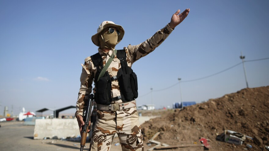 The Kurdish areas of northern Iraq have remained peaceful despite the recent surge in fighting. Here, a member of the Kurdish peshmerga forces directs traffic at a checkpoint in Kalak, in northern Iraq.