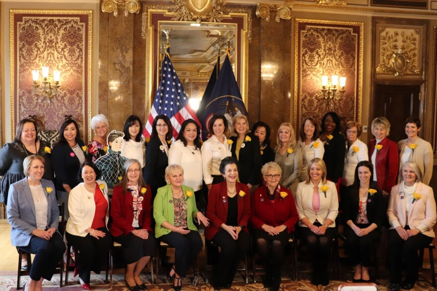 Photo of women in capitol wearing yellow roses.