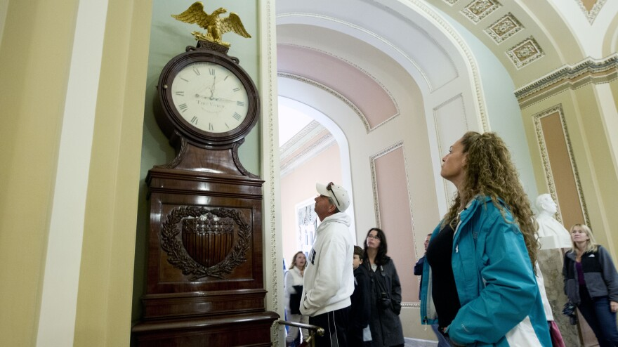 <strong>Still Right Twice A Day:</strong> Visitors look at the Ohio Clock outside the Senate chamber on Capitol Hill Sunday. The clock that has stood watch over the Senate for 196 years stopped running shortly after noon Wednesday. Employees who wind the clock weekly were furloughed in the federal shutdown.