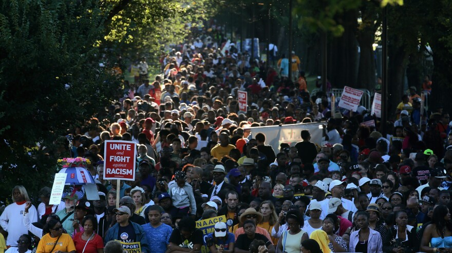 People hold signs as they gather to celebrate the 50th anniversary of the March on Washington.