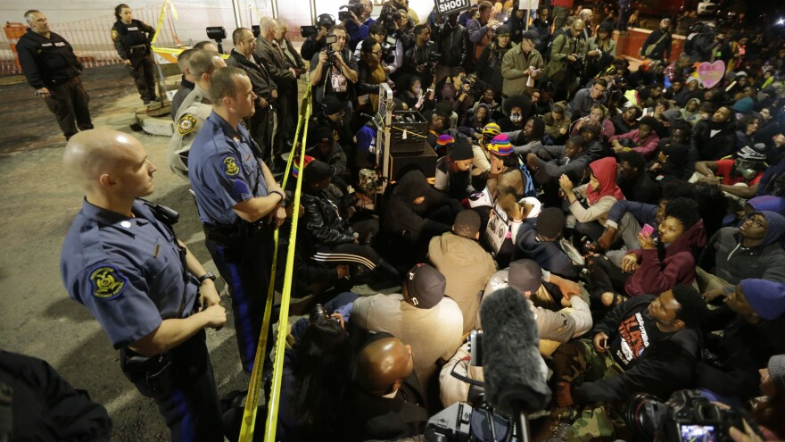 Protesters sit silently for over four minutes at the Ferguson Police Department Saturday, during a rally in remembrance of Michael Brown in Ferguson, Mo. While the demonstration was peaceful, police arrested protesters elsewhere.