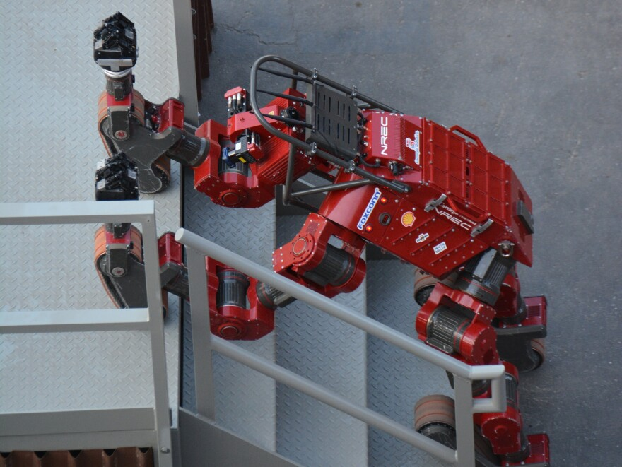 Carnegie Mellon's CHIMP uses its tracks to hoist itself up the stairs, completing the final task of the course.