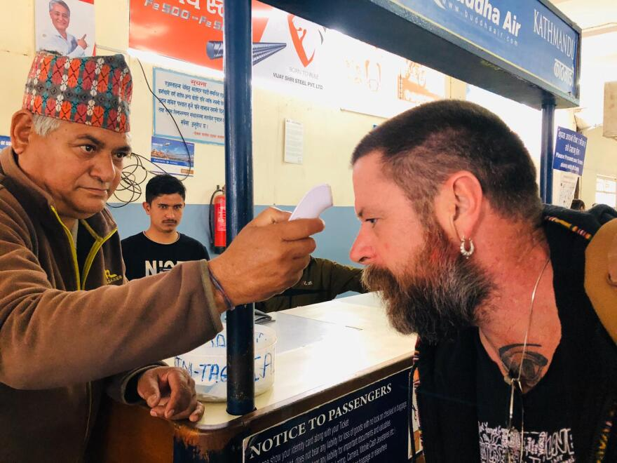 Man gets temperature taken prior to a regional flight lasting only 20 minutes in Nepal.