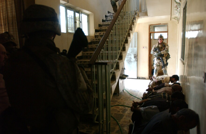 U.S. Marines guard arrested Iraqi men as they search a house in Fallujah during an offensive.