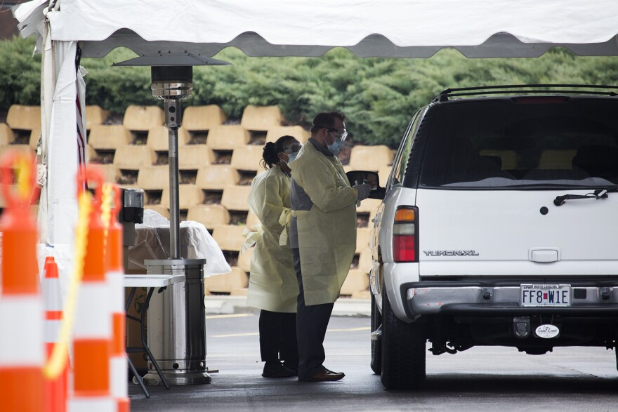Medical workers collect a sample from a patient at Mercy Health's drive-through coronavirus test center in Chesterfield in March. St. Louis County Executive Sam Page wants to purchase more tests for the county.