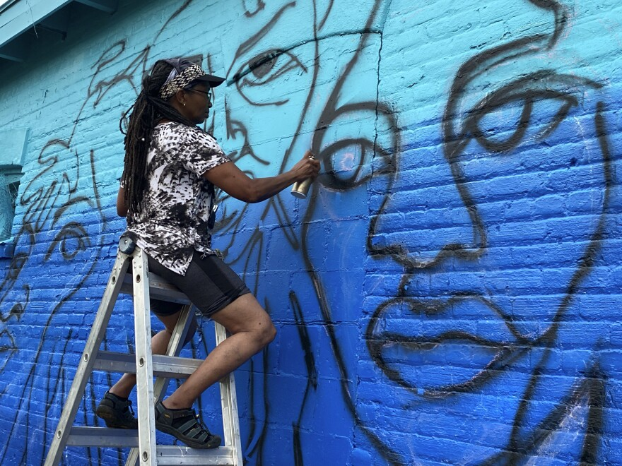 Artist Marsha Hatcher spray paints an outline for a Black Votes Matter mural, a project supported by Color Jax Blue, in Jacksonville, Fla.