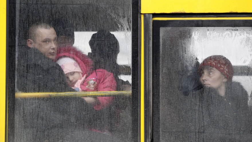 People wait on a bus to leave the town of Debaltseve, Ukraine, on Friday to escape the heavy fighting. Nearly 1 million Ukrainians have been displaced by battles between pro-Russian insurgents and government troops.