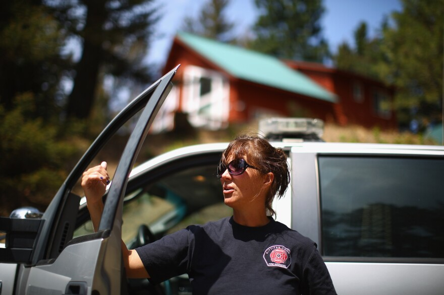 Brenda Larsen, fire marshal for Kittitas County, Wash., stands outside her patrol truck. She has already banned campfires and the burning of trash and leaves.