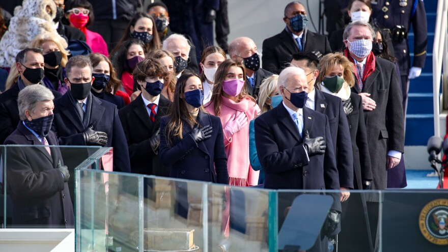 President-elect Joe Biden and invited guests stand for the national anthem and the Pledge of Allegiance at the inauguration ceremony on the West Front of the U.S. Capitol on Wednesday.