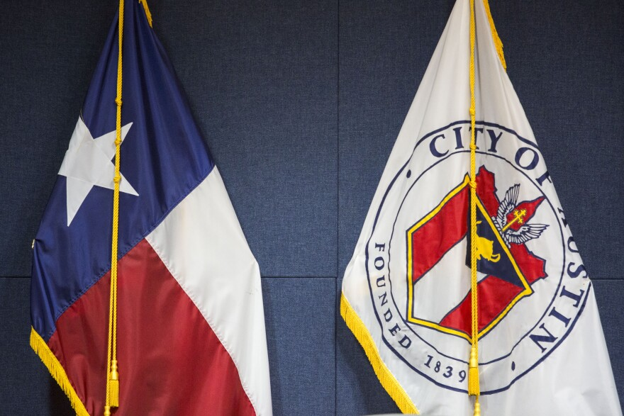 The Texas and City of Austin flags sit in the City Council Chambers at Austin City Hall.