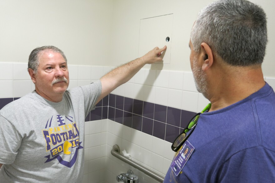 Boulder High custodian Allen Chavez shows a hole in the wall in a boy's bathroom where students deposit finished pods.  He said he finds pods thrown away all over the school, including in between furniture cushions.
