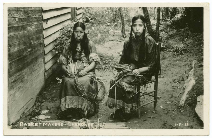 Archival image of two Cherokee women sitting on chairs, displaying basket making techniques and materials.