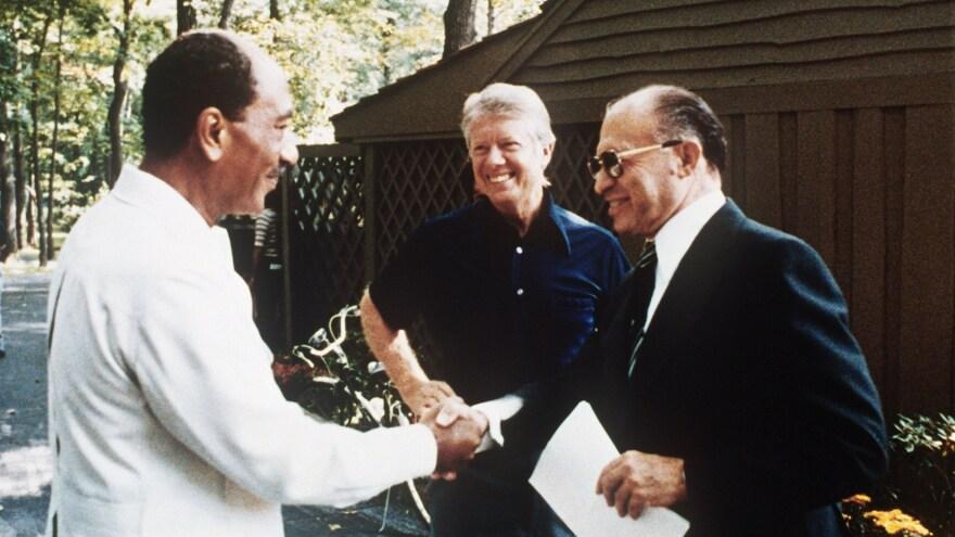 As President Jimmy Carter looks on, Egyptian President Anwar Sadat (left) shakes hands with former Israeli Prime Minister Menachem Begin at Camp David on Sept. 6, 1978.