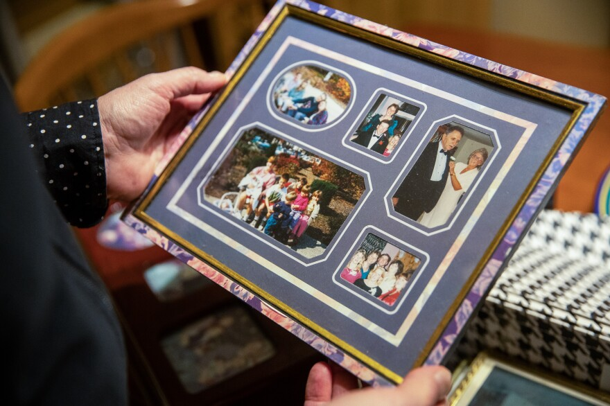 June Kelly holds a framed collection of photos of her mother, Marilyn Kelly.