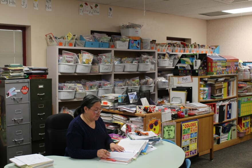 Dora Reyes sits at a desk with bookshelves full of learning materials behind her. The classroom is devoid of students.