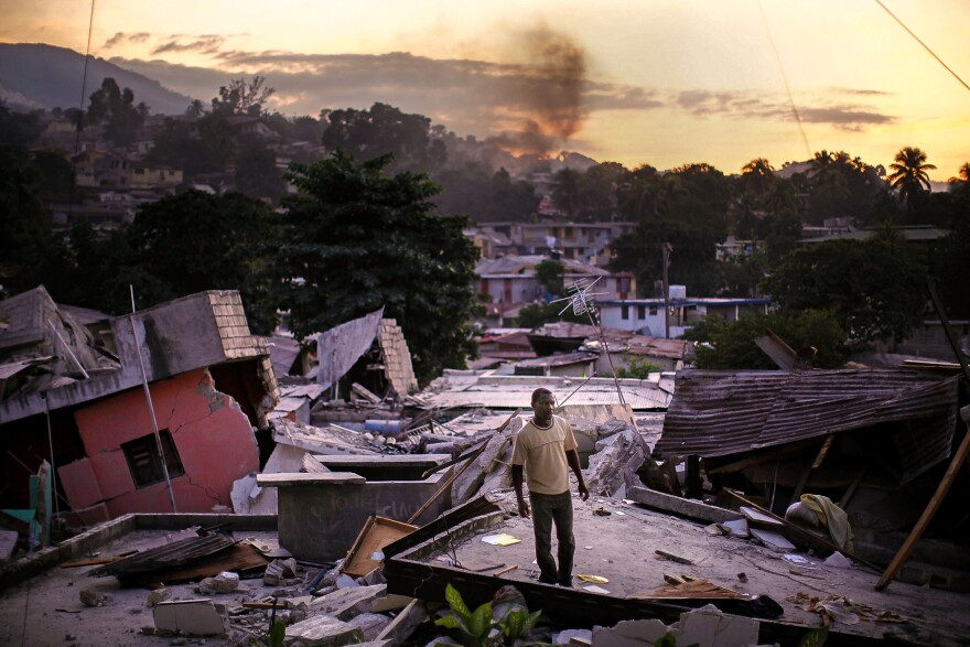 A man stands on rooftop in a leveled neighborhood yelling out for any sign of his missing relatives. It has been estimated that hundreds of thousands died in the disaster.