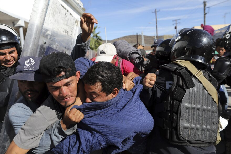 Migrants clash with Mexican police at the Mexico-U.S. border after getting past another line of Mexican police at the Chaparral crossing in Tijuana, Mexico, Sunday, Nov. 25, 2018, as they try to reach the U.S. The Tijuana mayor has asked the UN for aid.