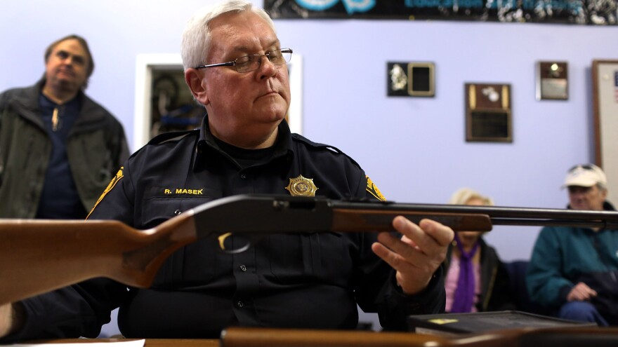 Police Lt. Ray Mesek registers a rifle at a gun buyback event on Saturday in Bridgeport, Conn.