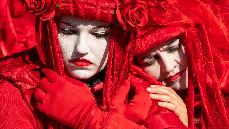 Extinction Rebellion supporters wear red costumes as they perform during a road block Monday in Berlin.