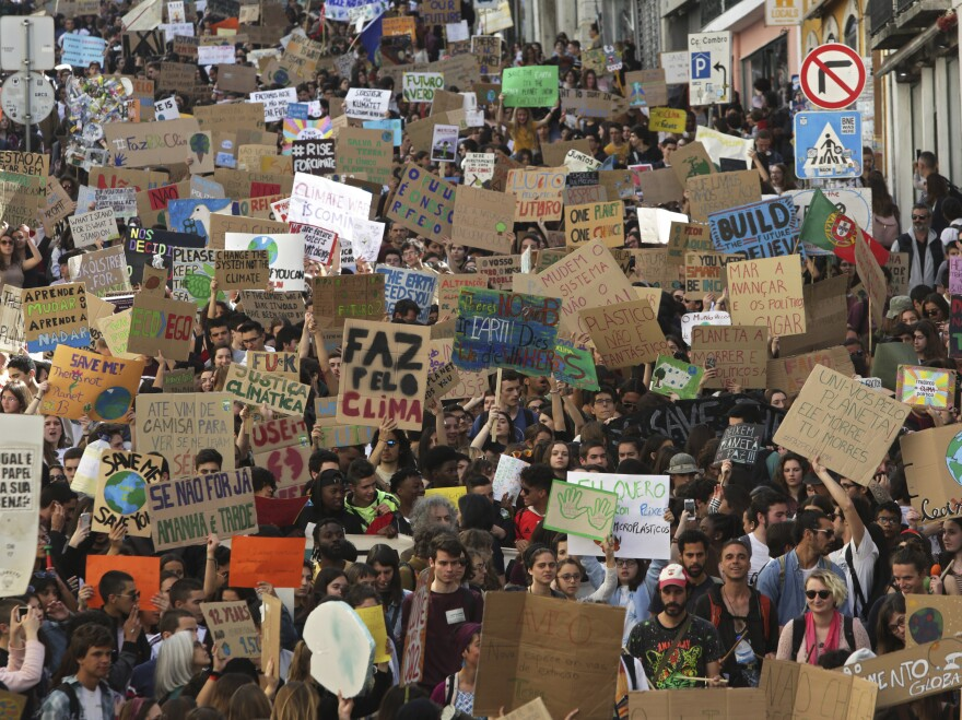 Students carry posters and chant slogans during a protest march through Lisbon, Portugal.
