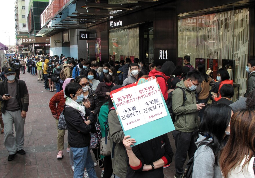 People queue up to buy masks in Hong Kong. The sign carried by the woman says masks are sold out.