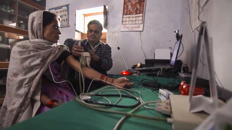 In the new program, a rural health care provider in India consults online with a doctor about a patient.