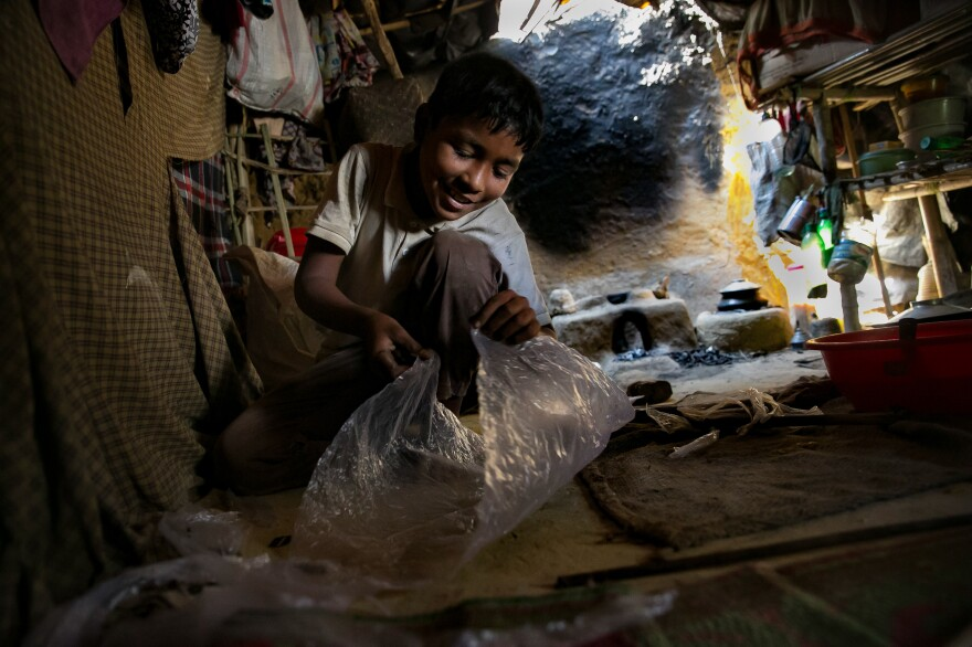 Ten-year-old Khamal makes a kite in his shelter in the camp. He gives the kites away to other kids.