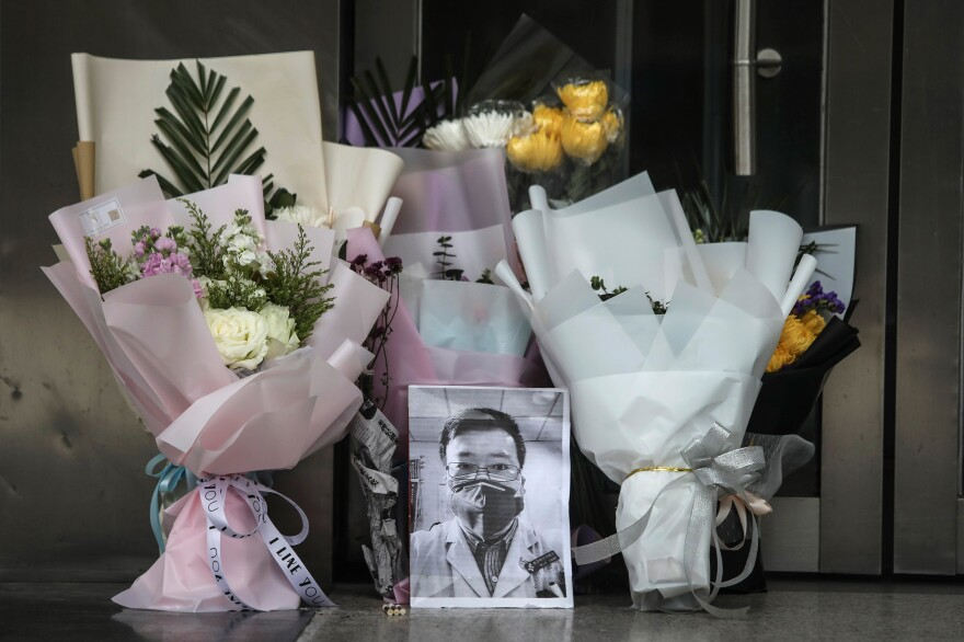 Flowers and a portrait of Dr. Li Wenliang is left at his hospital in Wuhan, China. Li, regarded a whistleblower in the coronavirus outbreak, died of the infectious disease on Friday.