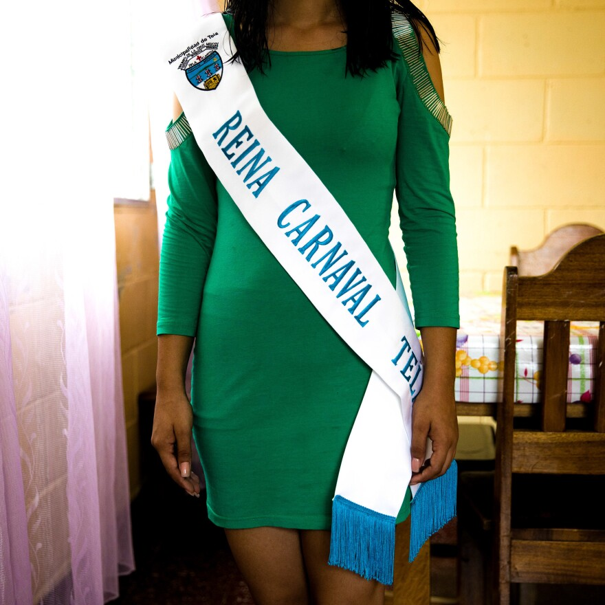 Naomi, who lives in house #9, shows off the sash she won in a competition to be queen of an anniversary festival at her school.