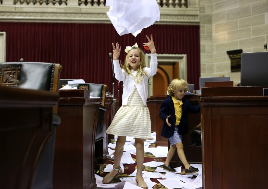 Margaux Harris, 7, granddaughter of Rep. Mike Lair, throws papers in the air shortly after members of the House did the same to mark the end of the legislative session.