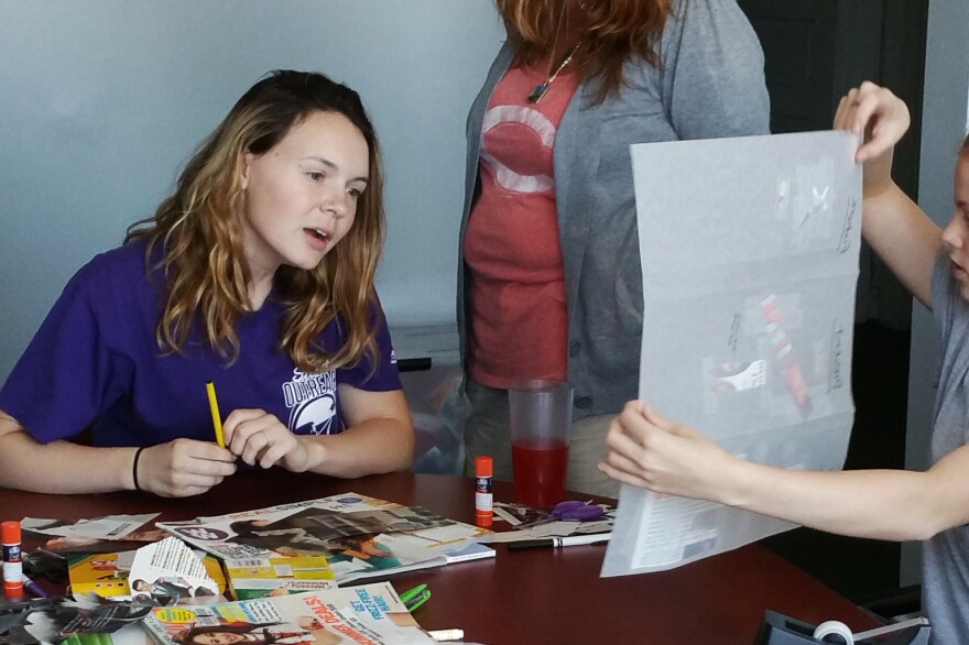 Kelsey Wasser (left) and Dawn Carson, street outreach supervisor (right), look at the artwork of one of the juveniles at the Homeward Bound Emergency Shelter in Covington, Ky.