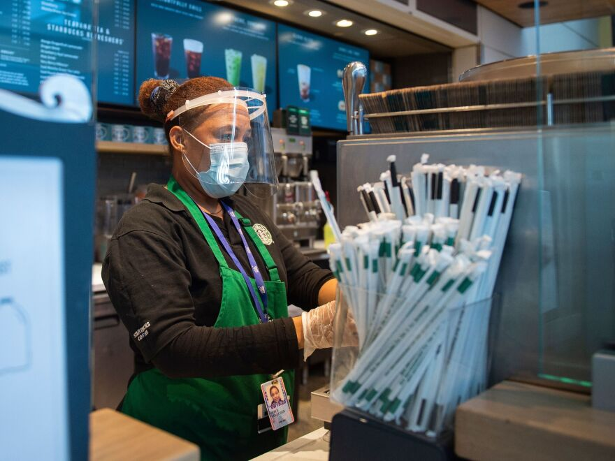 A Starbucks employee wears a face shield and mask as she makes a coffee drink at Ronald Reagan Washington National Airport in Arlington, Va., last week.