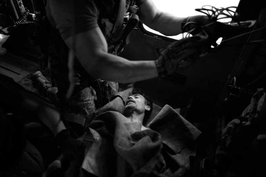 In flight to the hospital in southern Afghanistan, pararescue jumpers Andrew Rios (left) and Mark Bedell stabilize a local Afghan policeman injured in an improvised explosive device attack.