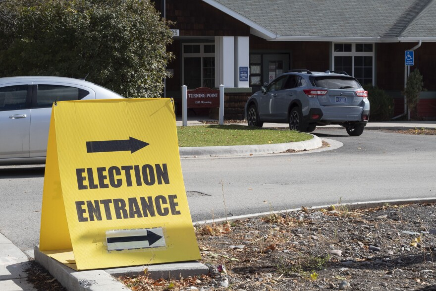 """A yellow sign with arrows and """"election entrance"""" in black points the way."""