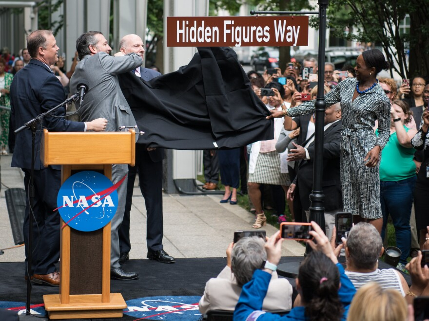 NASA Administrator Jim Bridenstine (from left), Sen. Ted Cruz, D.C. Council Chairman Phil Mendelson and Margot Lee Shetterly, author of the book <em>Hidden Figures,</em> unveil the Hidden Figures Way street sign at a dedication ceremony on Wednesday in Washington, D.C.