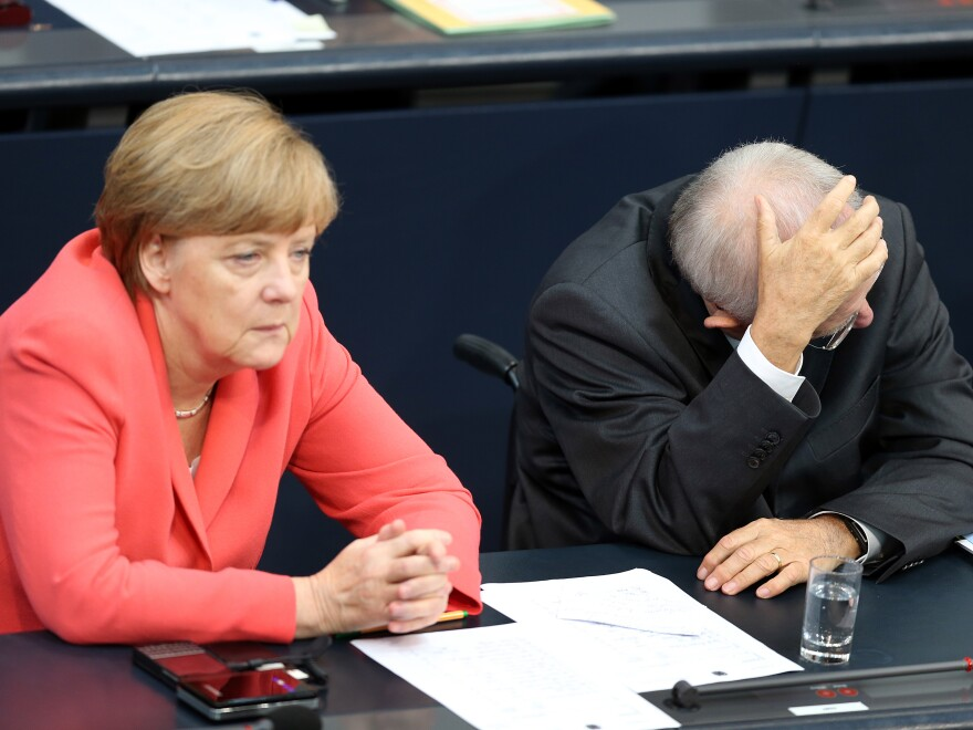German Chancellor Angela Merkel and German Finance Minister Wolfgang Schaeuble talk during a special meeting of the German parliament over the proposed bailout package for Greece.