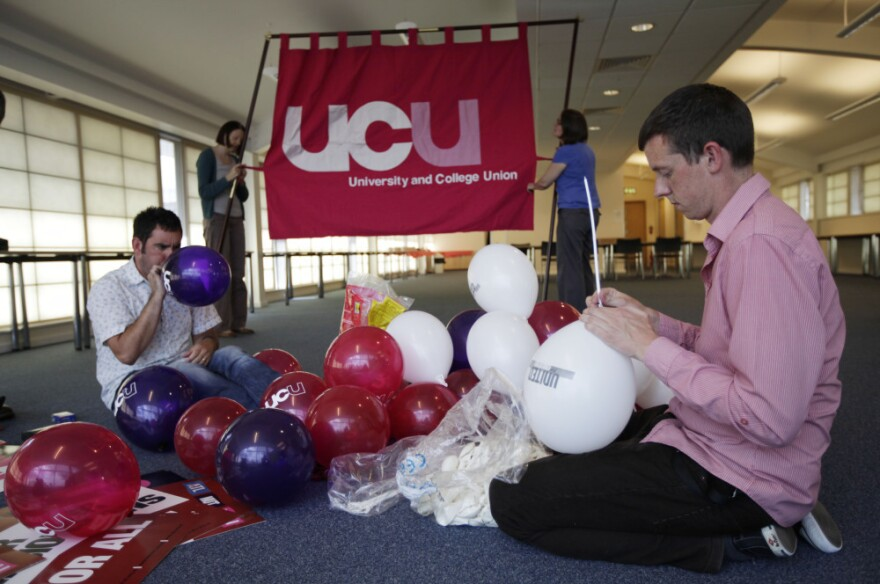 Members of Britain's University and College Union (UCU) pose for members of the media as they prepare for their union strike and march scheduled for Thursday.