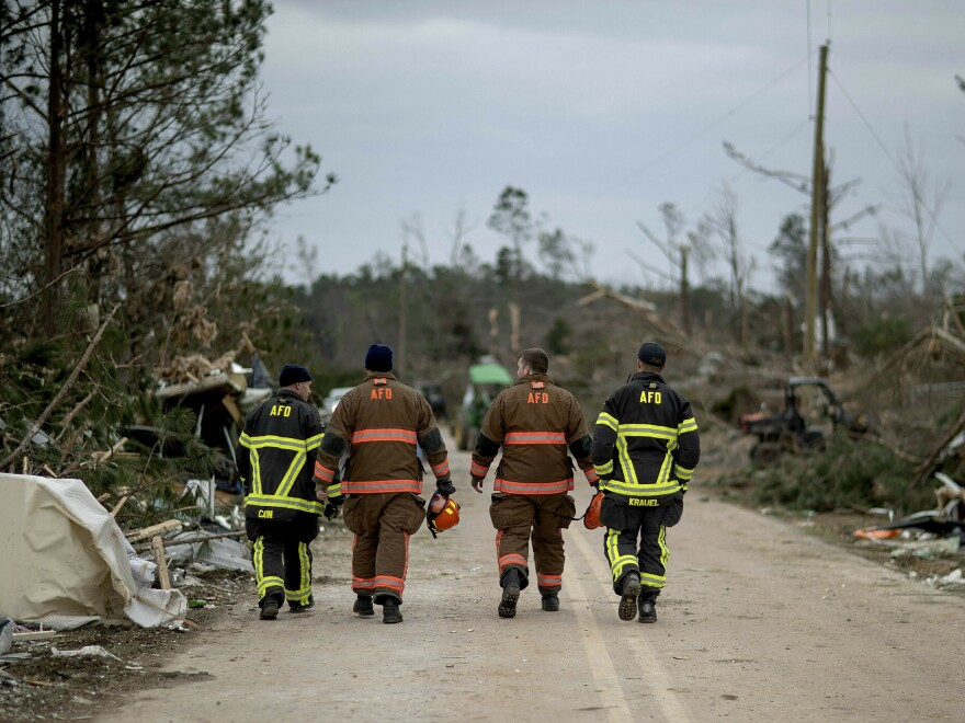 First responders walk through a neighborhood heavily damaged by a tornado the day before in Beauregard, Ala., on Monday. The death toll from the storm stands at 23, with victims ranging in age from 6 to 93.