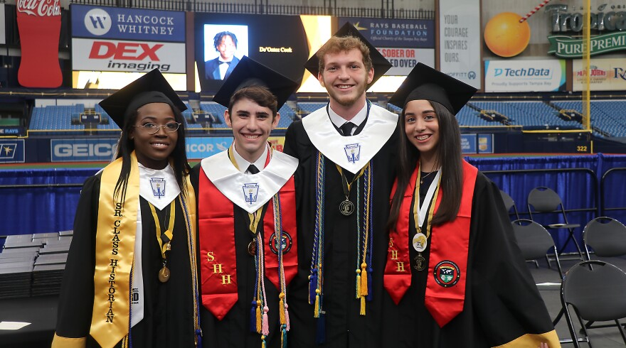 Four students stand together in graduation caps and gowns