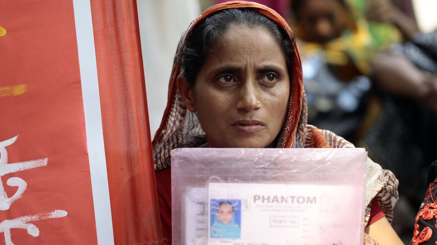 A Bangladeshi woman holds a photograph of a relative missing in the Rana Plaza building collapse, as she participates in a protest in Dhaka, Bangladesh, on Friday. Protesters demanded a minimum monthly salary of $103 and compensation for the victims and injured in the building collapse in April that killed more than 1,000 people.